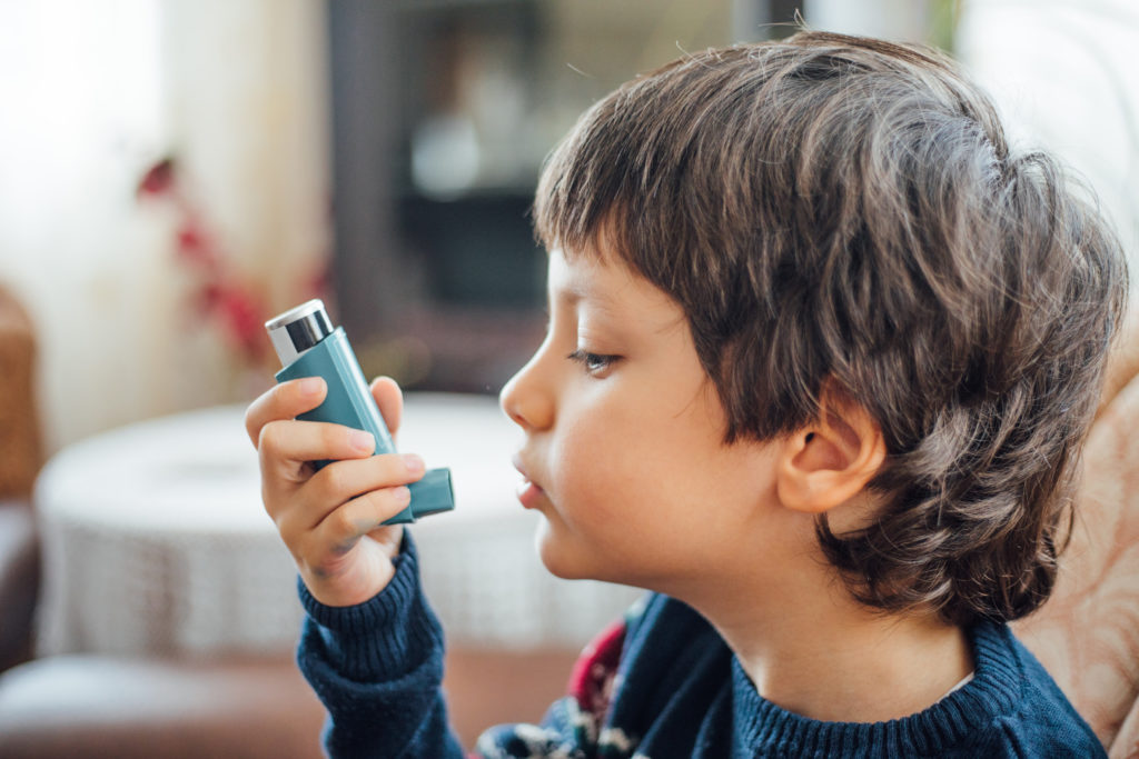 Young boy with asthma inhaler